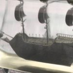 High resolution, detailed black ship model inside solid clear bottle